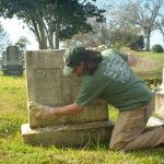 Instructor Jason Church cleans a marble headstone